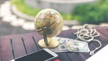 smartphone beside mini desk globe
