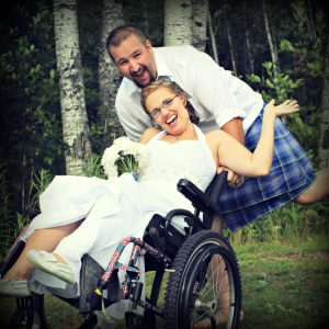Shawna and her husband Justin on their wedding day. He is tipping her back in her wheelchair.