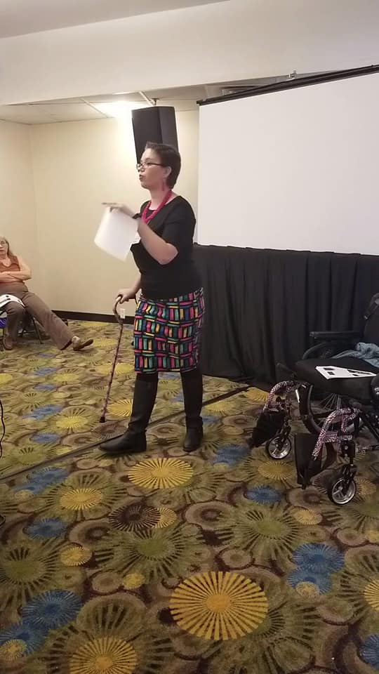 Adult female standing with a cane, holding a piece of paper, speaking in front of a group of people