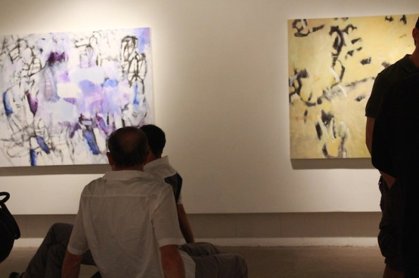 people looking at large abstract art
