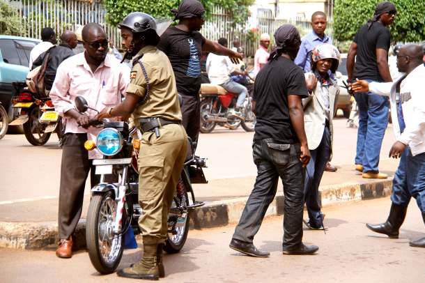 The unidentified men in black surrounding a boda boda cyclist after they beat him up and Deputy RPC Kampala south Geoffrey Tayeebwa assisting them to take the boda boda MONITOR PHOTO BY ABUBAKER LUBOWA