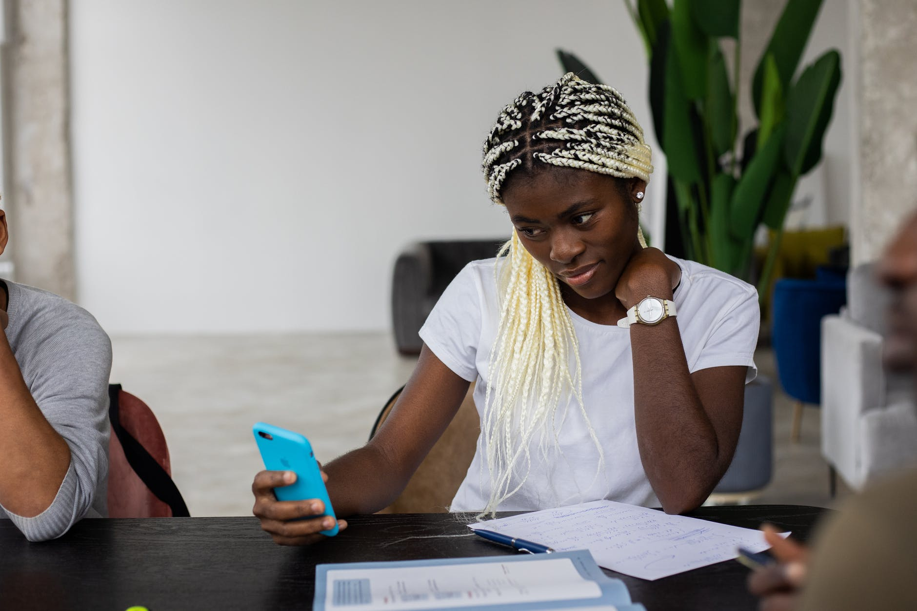 black woman using smartphone during teamwork with classmates