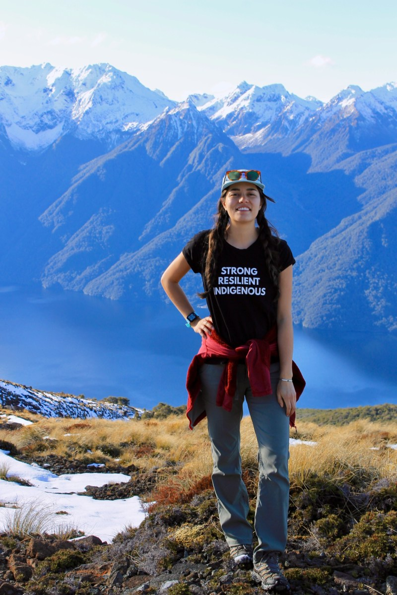 """Shaandiin Cedar standing wearing a """"Strong, Resilient, Indigenous"""" shirt with mountains in the background."""