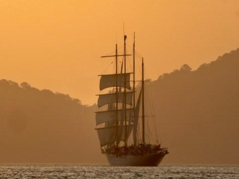 Ein traditioneller Rahsegler mit 4 Masten segelt im Sonnenuntergang vor Koh Adang an uns vorbei.