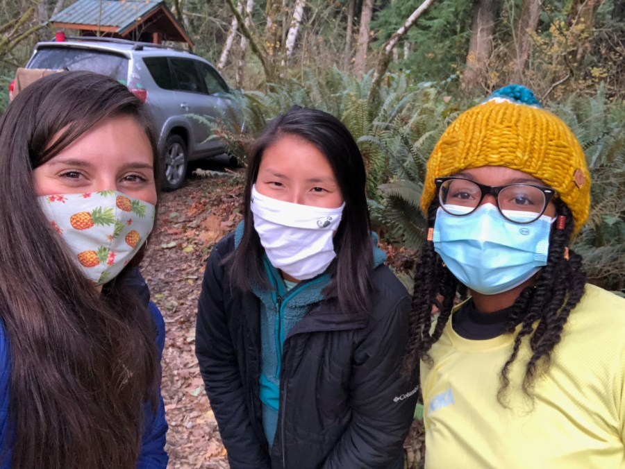 Three masked women (one white, one Asian, one Black) look into the camera. In the background are a dirt road, car, and ferns.