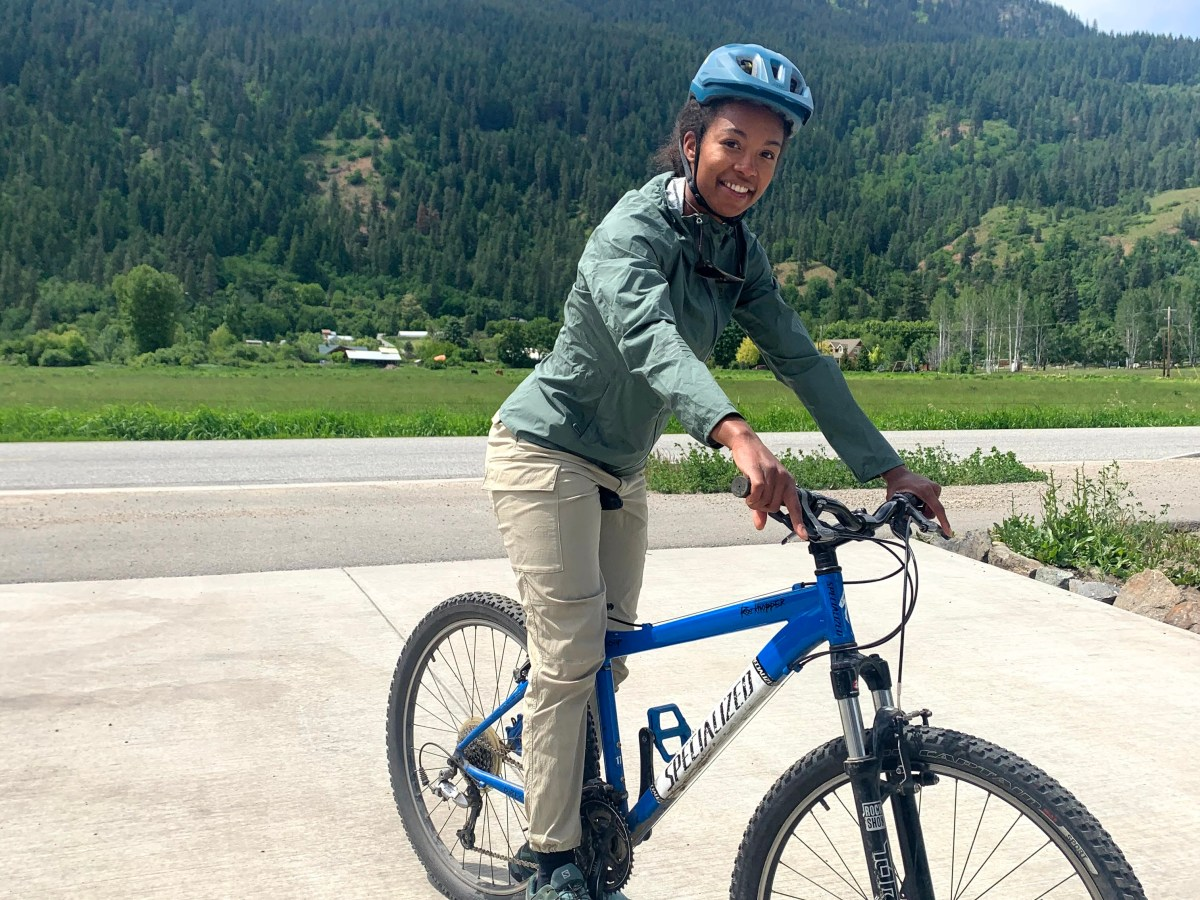 Chelsea the author and founder of Shecolorsnature on a blue mountain bike in front of her home. She has on a green bike helmet, rain coat and shoes. She is smiling because she just got home from a bike ride with her oldest daughter.
