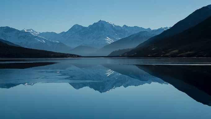 calm body of lake between mountains