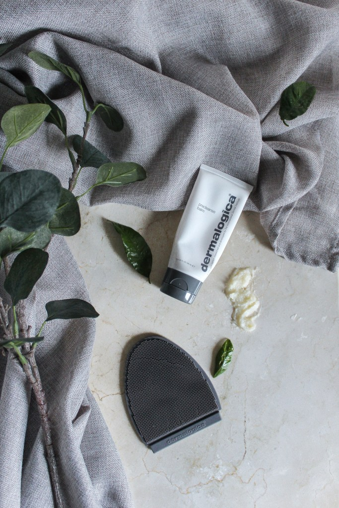 A Dermalogica Pre-cleansing balm, cleansing glove, and a sample of the balm neatly placed on the bathroom counter top with a grey towel and a green flower branch