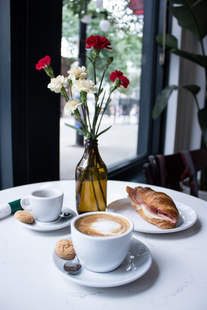 Italian coffee served with biscuits and a croissant on a table with flowers