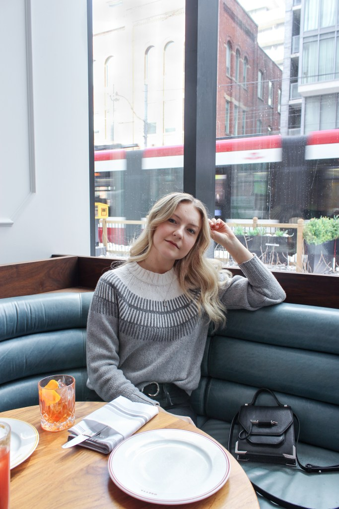 A blonde woman posing in an Everlane ski sweater inside a Toronto restaurant with a drink placed in front of her