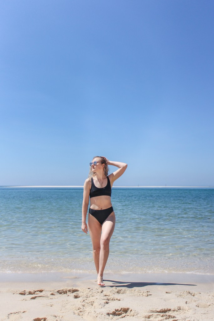 A blonde woman wearing a black bikini stepping out of the turquoise waters of the Natural Park of Arrabida