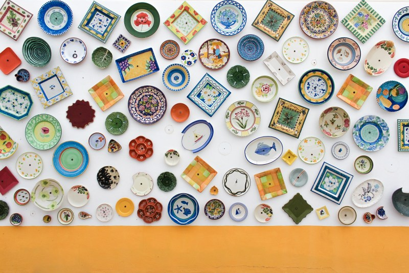 A colourful collection of different-sized plates decorating the wall of a pottery shop in Sagres