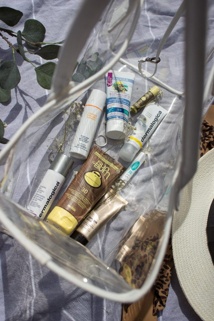Sunscreens of different types, sizes and colours as seen from the top through a clear beach bag