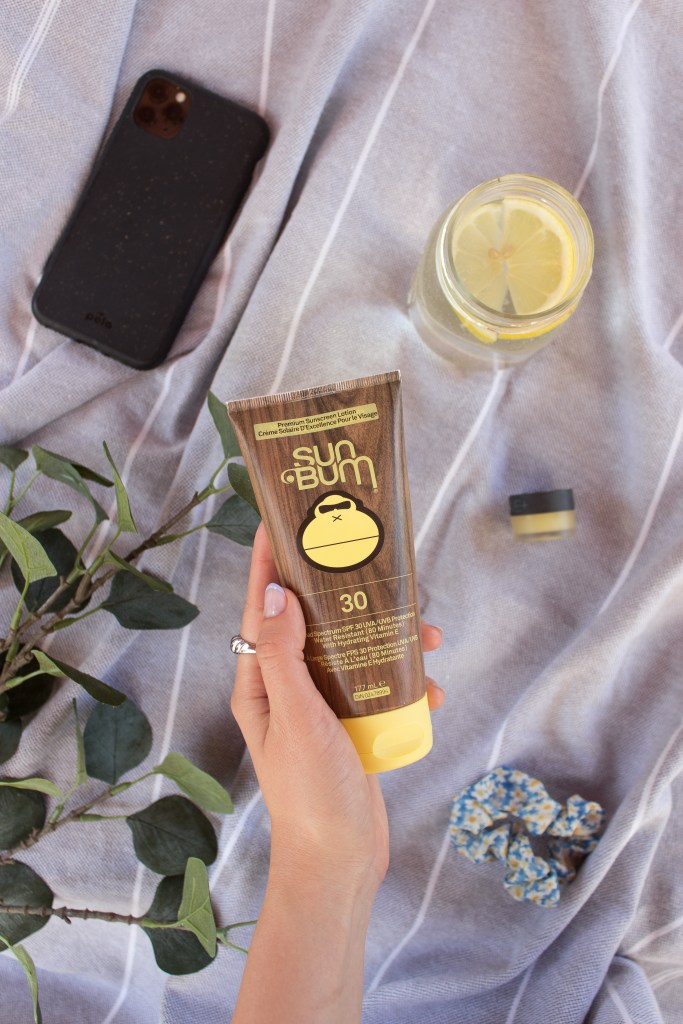 "A hand holding the ""Original SPF 30 Moisturizing Sunscreen Lotion "" by Sun Bum with a phone, lemon water, scrunchie, lip balm and leafed branches in the background"