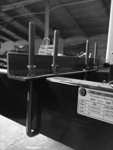 Automotive U-bolts that anchor the mini-split condenser unit to the trailer toungue
