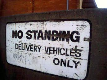 sign that says 'no standing, delivery vehicles only'