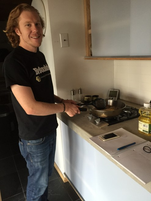 Ryan Militello-Hourigan cooking an egg in the passive house.