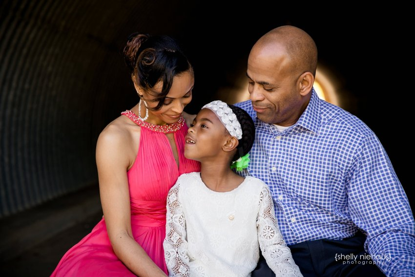 mom and dad smiling down at little girl - prosper family portraits