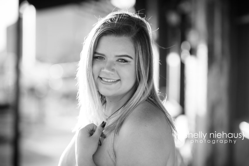 Fun downtown senior girl session with rustic buildings + silos in Texas.