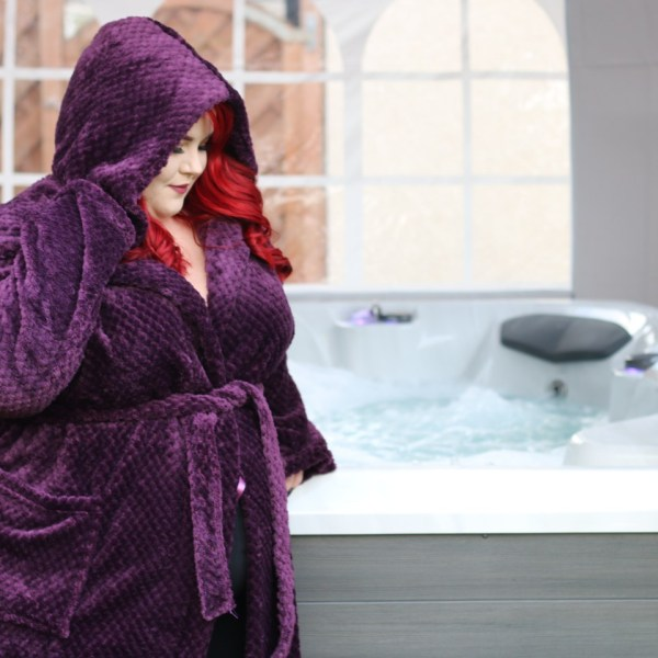 Georgina, size 24, in a purple robe in front of a hot tub in the garden