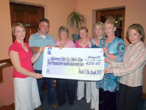 Joe Flannery (festival chairman) presents cheque to Breda Devaney of the Azheimers Unit at St. John's