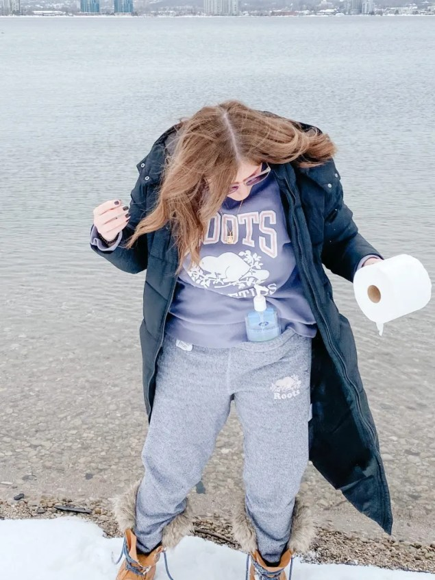 Woman on the beach in a track suit holding toilet paper and hand sanitizer