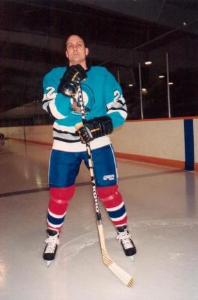 This i a photo of a middle-aged Caucasian man in a hockey uniform holding a stick on an ice rink