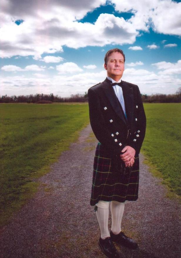 This i a photo of a middle-aged Caucasian man in a kilt and jacket, standing in a field