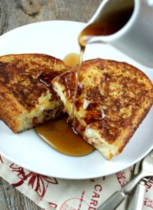 Syrup pouring over French Toast on white plate