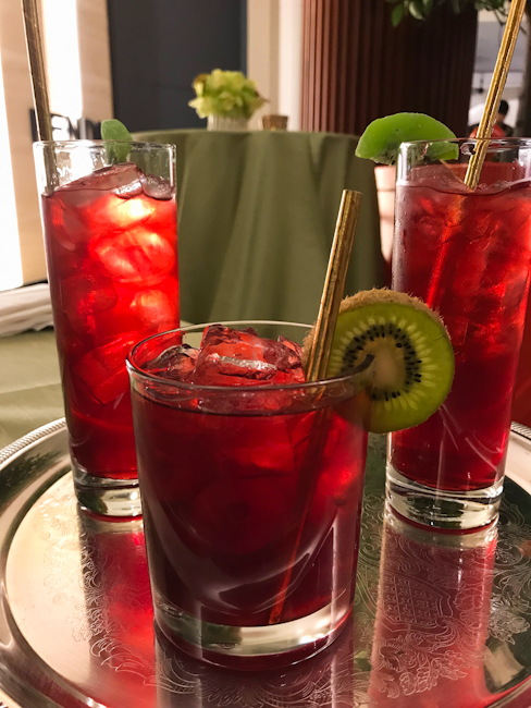Crimson colored vodka cocktails decorated with kiwi