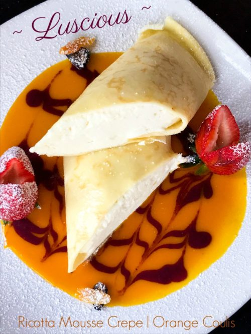 Ricotta Mousse Crepe Orange Coulis, Brown Butter design and Strawberries on white plate