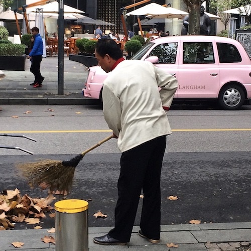 Man sweeping street in front of the Langham Hotel in Shanghai
