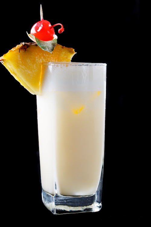 Pina Colada cocktail with pineapple and Maraschino cherry garnish agains a black background