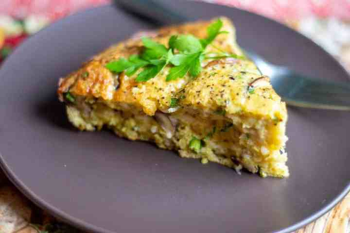 slice of mushroom frittata with parsley garnish and fork sitting on a brown plate