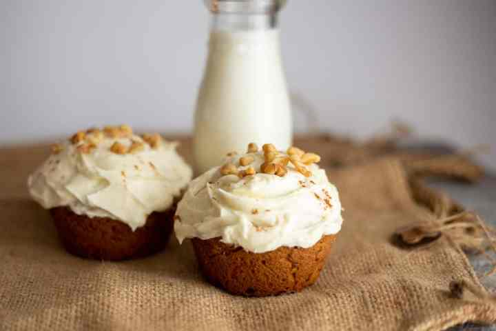two jumbo carrot muffins on burlap cloth with milk in background