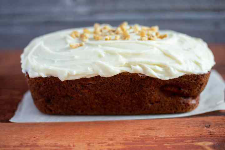 banana bread with cream cheese icing on parchment paper