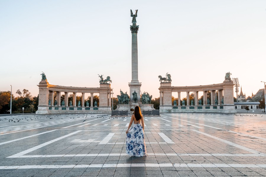 Girl in a blue floral dress standing in the middle of the Heroes Square in Budapest