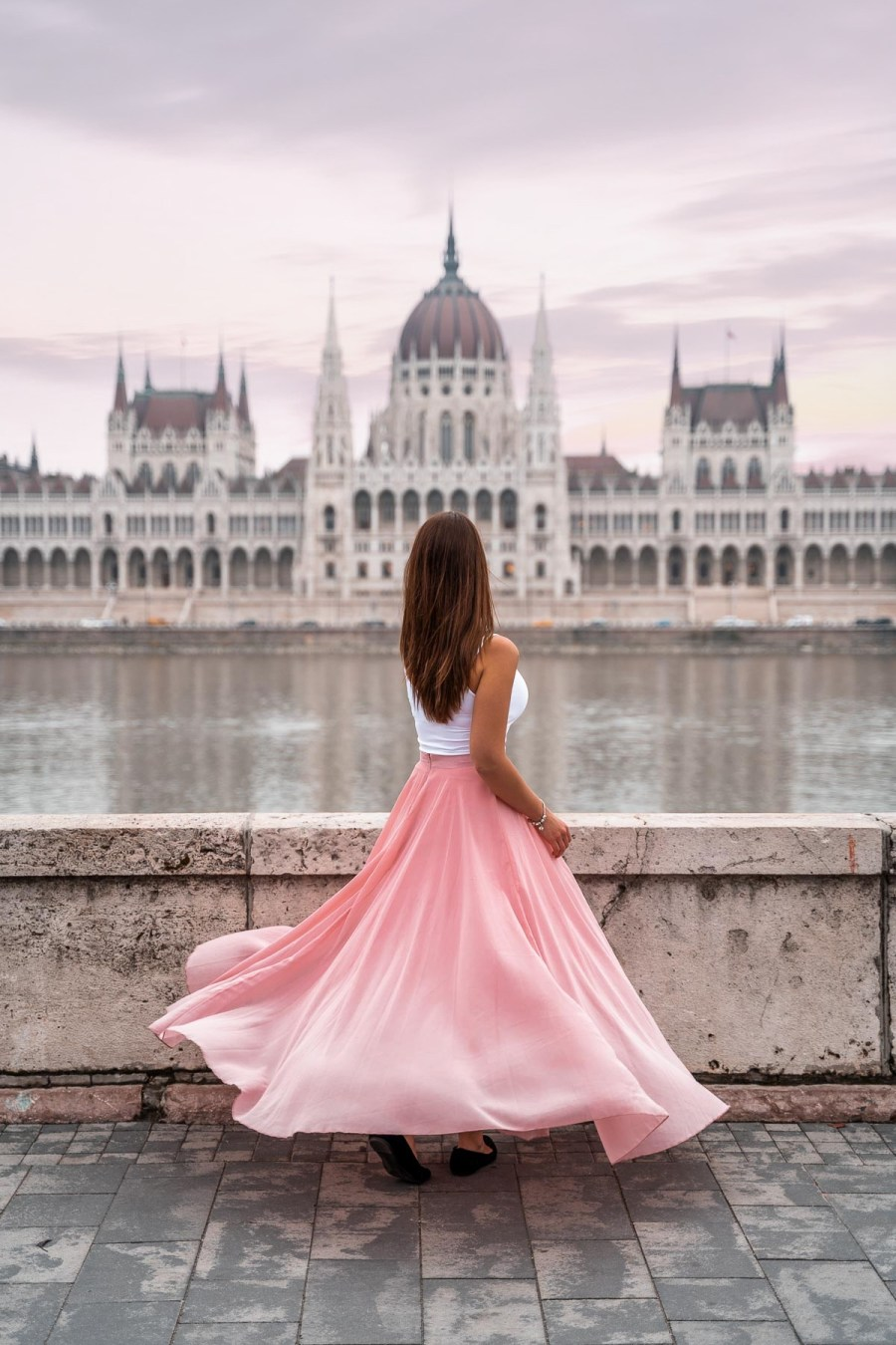 Girl in a pink skirt twirling in front of the Hungarian Parliament at one of the best Budapest Instagram Spots