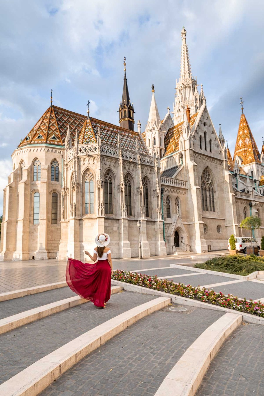 Girl in a red skirt standing in front of Matthias Church in Budapest