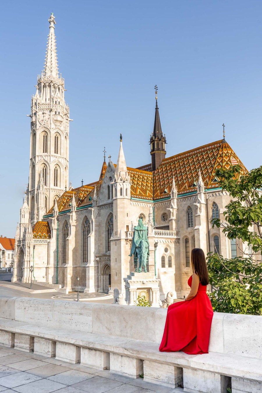 Girl in a red dress sitting in front of the Matthias Church in Budapest