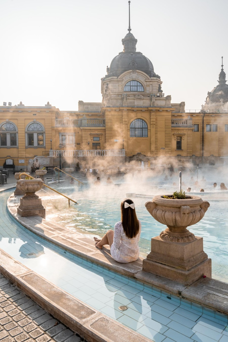 Girl in a white dress sitting at the edge of the pool in the Szechenyi Thermal Bath in Budapest