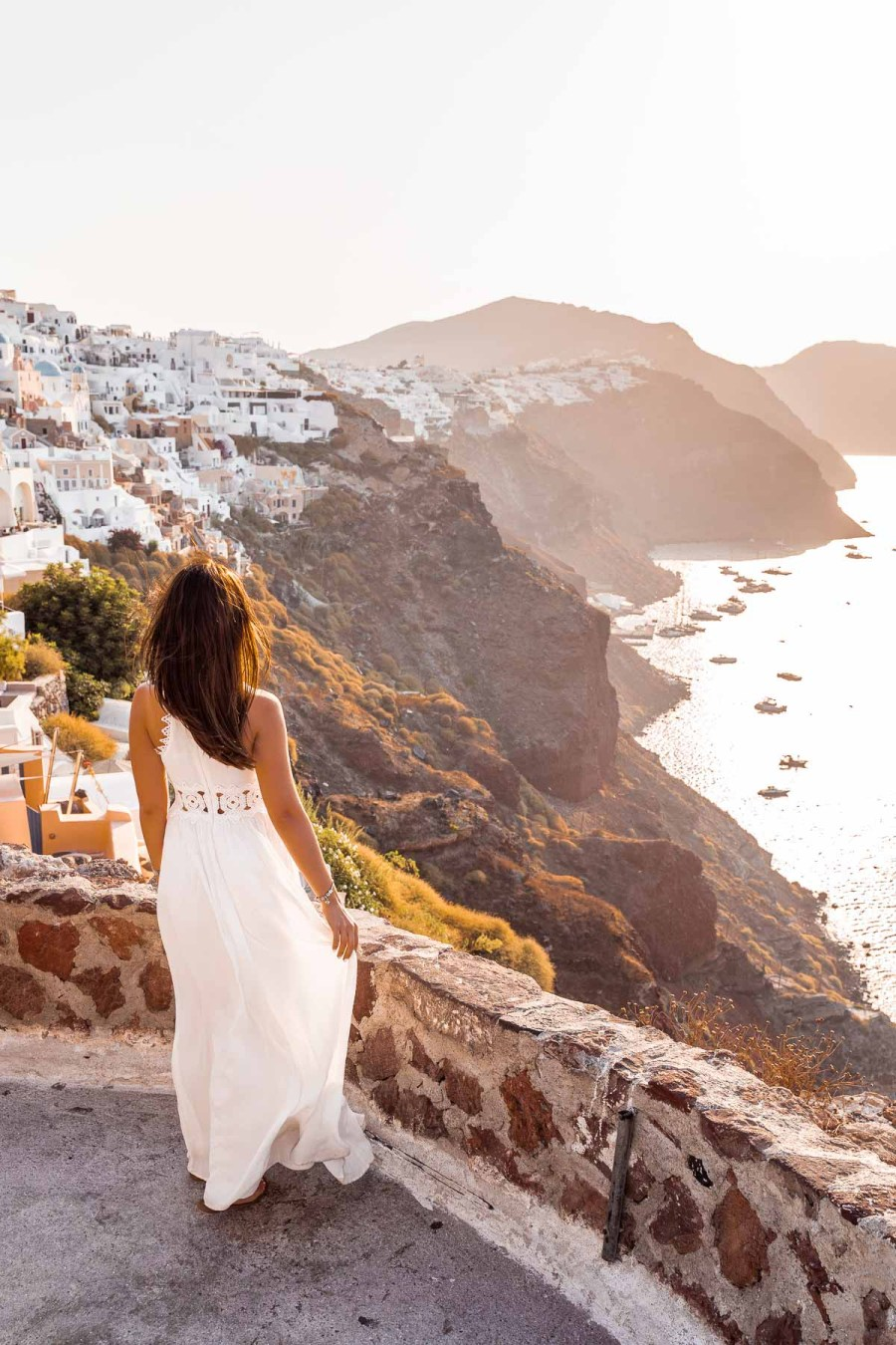 Girl in a white dress standing in the Oia Castle, looking at the view of the caldera at sunrise