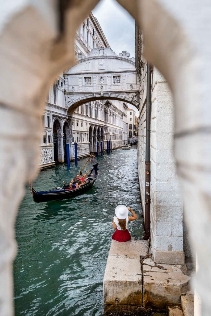Girl in a red skirt sitting below the Bridge of Sighs in Venice, Italy