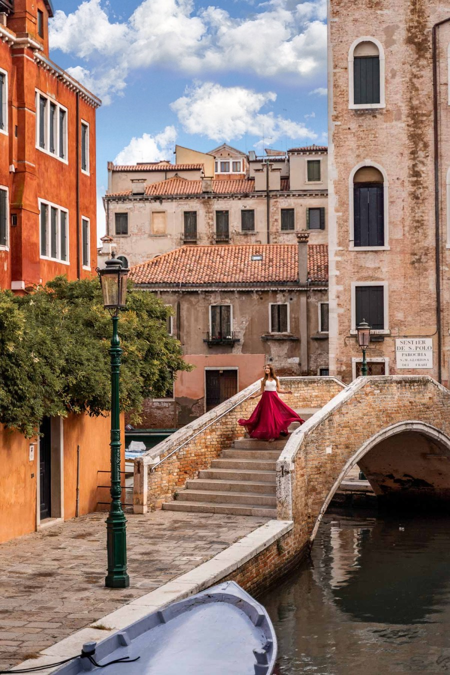 Girl in a red skirt twirling on a bridge in front of Campo San Boldo in Venice, Italy