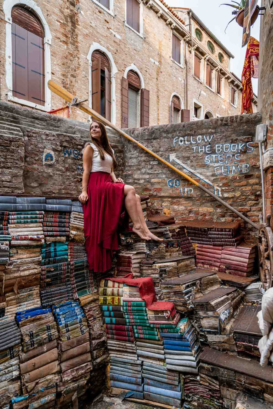 Girl in a red skirt sitting on top of the books at Libreria Acqua Alta in Venice, Italy