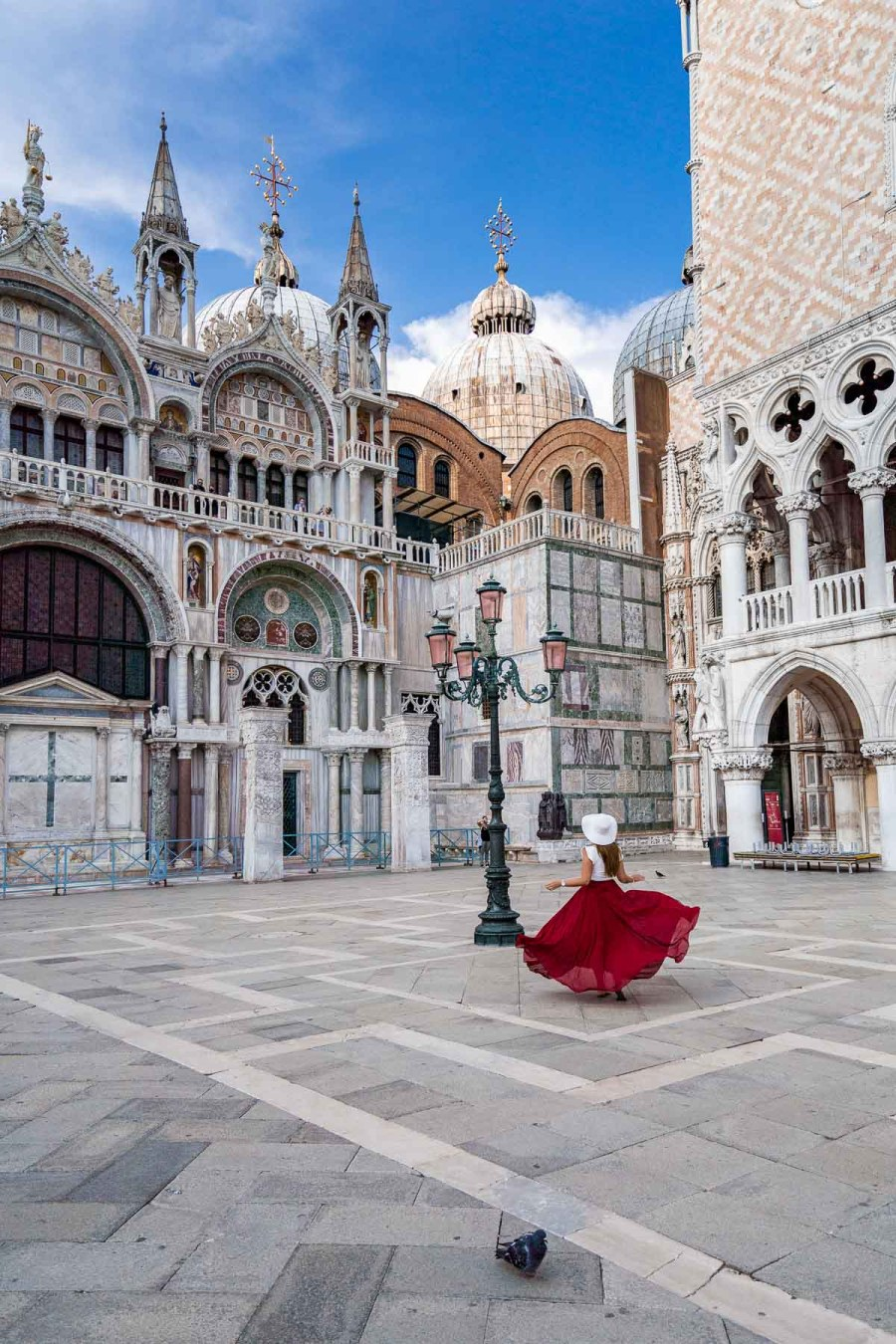 Girl in a red skirt twirling in St. Mark's Square in Venice, Italy
