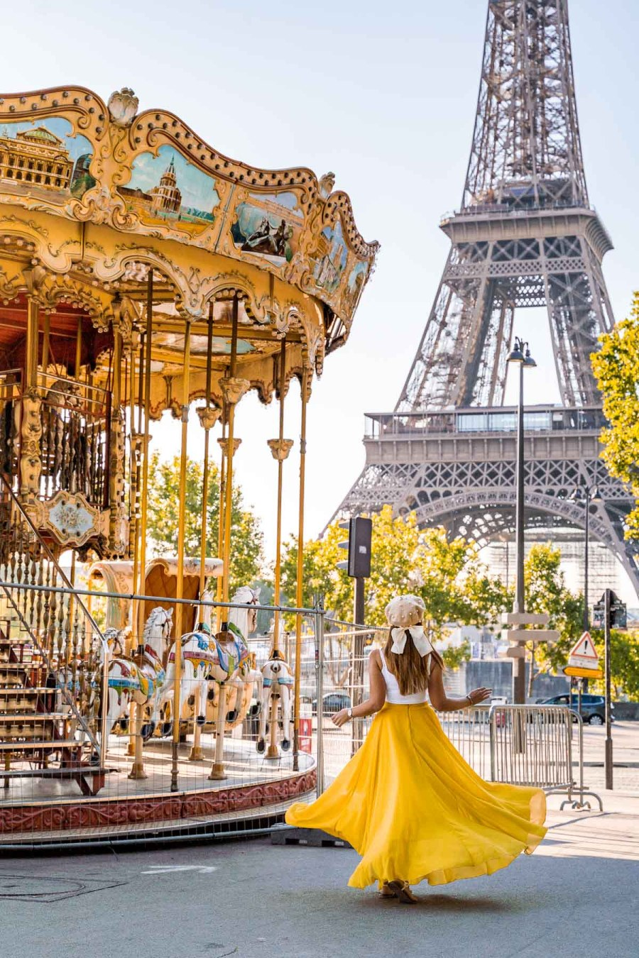 Girl in a yellow skirt twirling in front of a carousel near the Eiffel Tower in Paris
