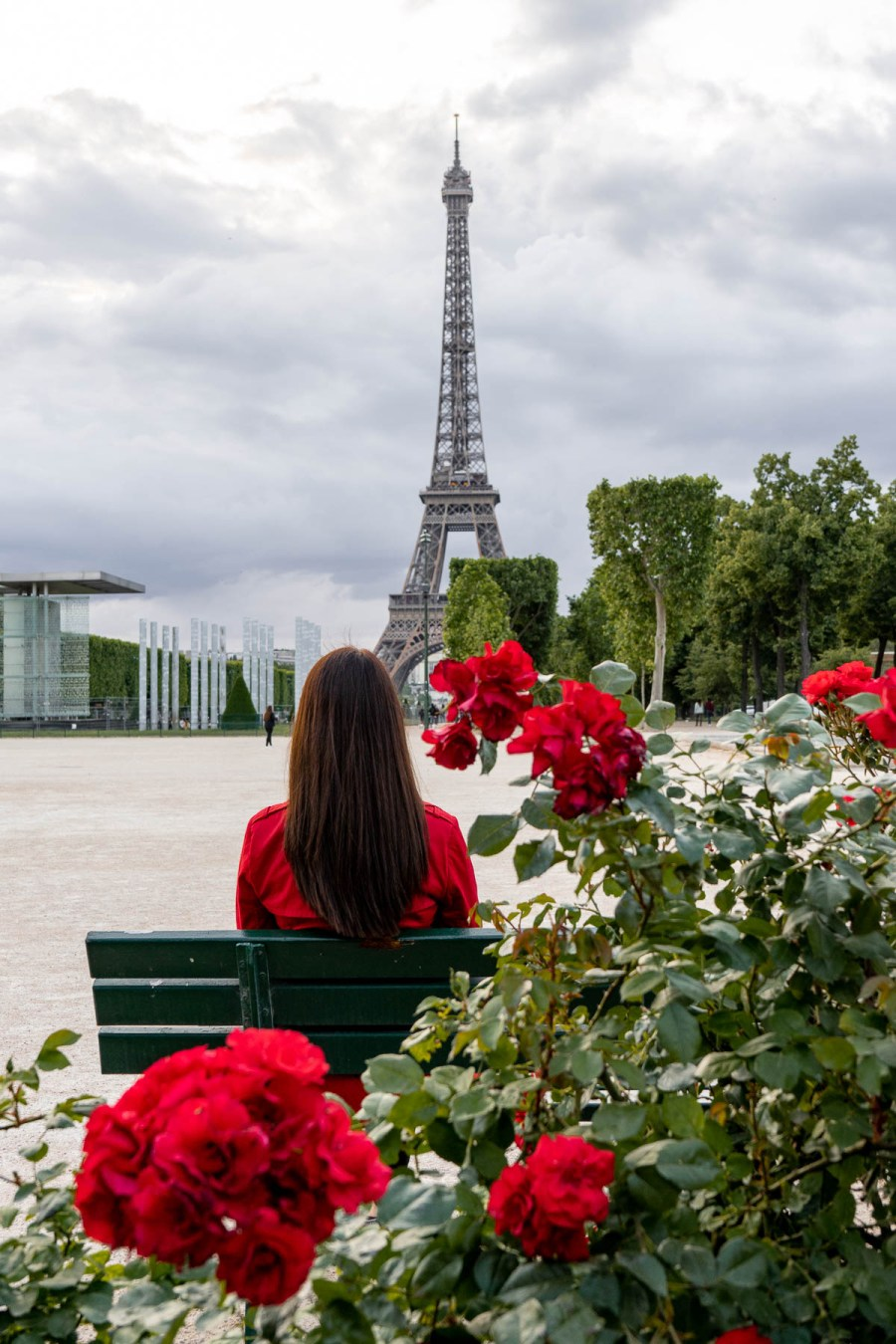 Girl in a red coat sitting on a bench, looking at the Eiffel Tower at Champ de Mars