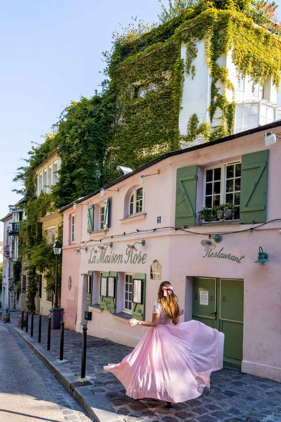 Girl in a pink skirt twirling in front of La Maison Rose in Montmartre, Paris