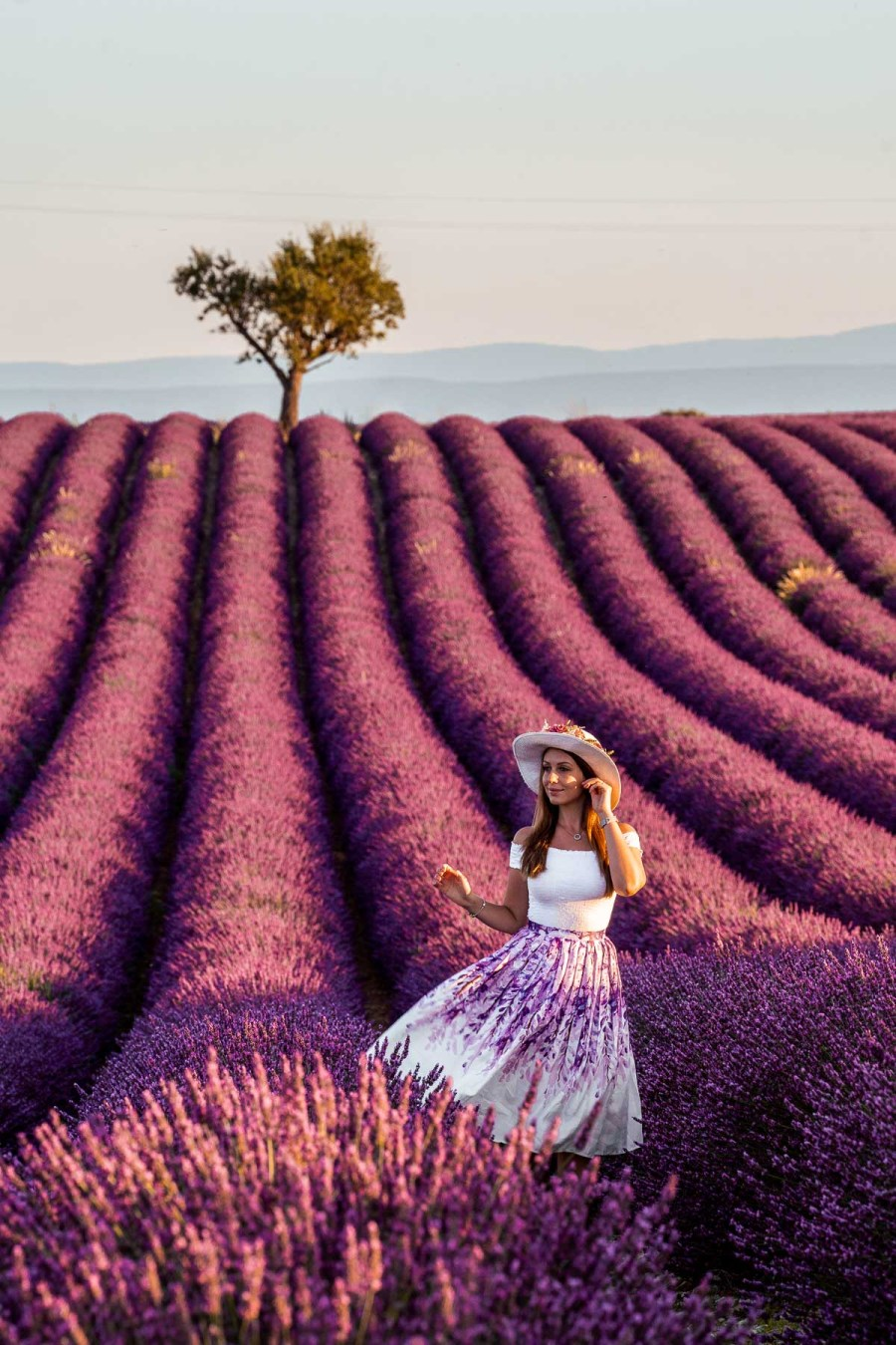 Girl in a purple skirt standing in the lavender fields with a heart shaped tree in the background in Provence